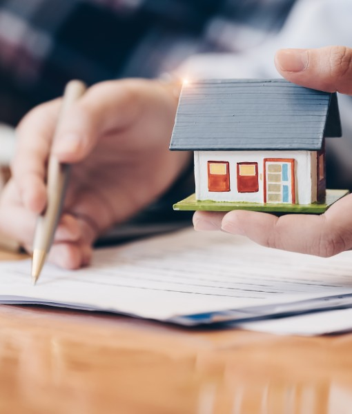 Hands with paperwork and small house model